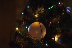 Close-up de um ornamento da quinquilharia do Natal e de umas luzes coloridas em uma árvore de abeto Imagem de Stock Royalty Free