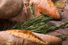 Close-up de um pão fresco, crocante, natural Baguette e verdes em um fundo de madeira Ingredientes do café da manhã na tabela Foto de Stock Royalty Free