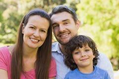 Close up de um par de sorriso com o filho no parque fotografia de stock