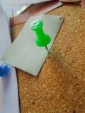 Close up de um pino verde que fixa um papel com uma almofada de cortiça embaixo fotos de stock