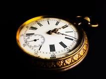Close-up de um relógio velho isolado em um fundo preto grampeado fotografia de stock royalty free
