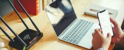 Close up de um router sem fio e de um homem que usa o smartphone no ofiice da sala de visitas em casa, wifi dos conceitos para co imagem de stock