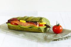 Close-up de um sanduíche com salmões, abacate, ervas e tomates Imagens de Stock Royalty Free