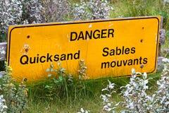 Close up de um sinal bilíngue da areia movediça do perigo Imagem de Stock Royalty Free