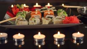 Close-up de um sushi em uma placa quadrada com vela vídeos de arquivo