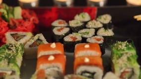 Close-up de um sushi em uma placa quadrada com vela filme