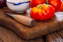 Close up de um tomate da carne e de uma faca de cozinha Fotografia de Stock