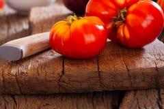Close up de um tomate da carne e de uma faca de cozinha Fotografia de Stock Royalty Free