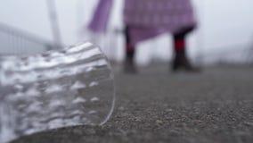 Close-up de um vidro que encontra-se no pavimento Figura confidencial de uma mulher adulta nos farrapos que anda no borrada vídeos de arquivo