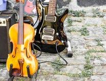 Close-up de um violino e de uma guitarra elétrica envernizada preta em uma feira da ladra fotografia de stock