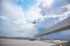 Close-up de um voo do avião comercial sobre uma estrada contra um céu azul fotos de stock royalty free