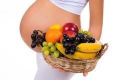 Close-up de uma barriga grávida e de uma cesta de frutos exóticos Foto de Stock
