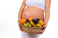 Close-up de uma barriga grávida e de uma cesta de frutos exóticos Fotos de Stock