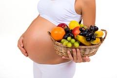 Close-up de uma barriga grávida e de uma cesta de frutos exóticos Imagens de Stock Royalty Free