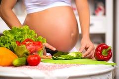 Close-up de uma barriga grávida Mulher gravida na cozinha que prepara uma salada vegetal Imagens de Stock