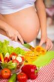 Close-up de uma barriga grávida Mulher gravida na cozinha que prepara uma salada vegetal Fotografia de Stock Royalty Free