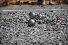Close up de uma bola de aço para o petanque que bate a superfície do cascalho, Fotos de Stock Royalty Free