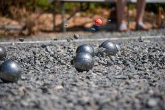 Close up de uma bola de aço para o petanque que bate a superfície do cascalho, Fotografia de Stock
