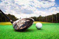 Close-up de uma bola de golfe e de uma madeira do golfe Foto de Stock