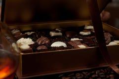 Close up de uma caixa do chocolate completamente de confeitos belgas e de um vidro Foto de Stock Royalty Free
