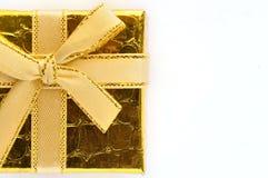 Close up de uma caixa de presente dourada em um fundo branco Imagens de Stock