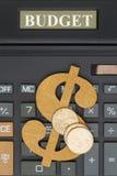 Close-up de uma calculadora com um sinal de dólar e as moedas de ouro Fotos de Stock