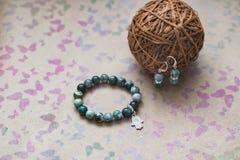 Close-up de uma colar e de brincos do jaspe e da prata verdes em um fundo com borboletas multi-coloridas Foto de Stock