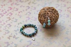 Close-up de uma colar e de brincos do jaspe e da prata verdes em um fundo com borboletas multi-coloridas Imagens de Stock