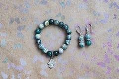 Close-up de uma colar e de brincos do jaspe e da prata verdes em um fundo com borboletas multi-coloridas Imagens de Stock Royalty Free