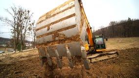 Close-up de uma cubeta da m?quina escavadora que jogue para fora a terra Movimento lento de um escavador que escava um po?o e que filme