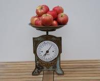 Close up de uma escala nostálgica da cozinha com as maçãs na bandeja de escalas foto de stock