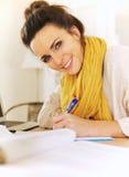 Escrita alegre da mulher em seu jornal fotografia de stock royalty free