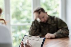 Close-up de uma escrita da mão em um pedaço de papel com um soldado deprimido no fundo borrado fotografia de stock