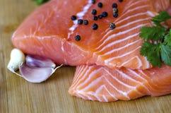 Close up de uma faixa salmon fresca com ervas e alho Fotos de Stock Royalty Free