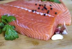 Close up de uma faixa salmon fresca com ervas e alho Fotografia de Stock Royalty Free