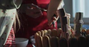 Close-up de uma família que decora um bolo do feriado na cozinha video estoque