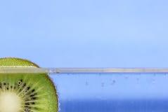 Close up de uma fatia do quivi que flutua na água gasosa contra um fundo do azul do aqua Fotos de Stock Royalty Free