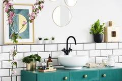 Close-up de uma flor, do gráfico na parede e da bacia de lavagem em um armário de turquesa Foto real imagem de stock royalty free