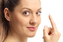 Close-up de uma jovem mulher com a lente de contato em seu dedo imagem de stock
