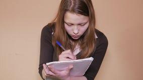 Close-up de uma jovem mulher esgotada que trabalha ou que prepara-se para seu exame vídeos de arquivo