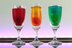 Close up de uma linha de cocktail coloridos que descansam na barra com iluminação conduzida em um clube Fotografia de Stock