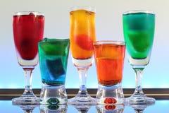 Close up de uma linha de cocktail coloridos que descansam na barra com iluminação conduzida em um clube Fotografia de Stock Royalty Free