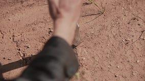 Close-up de uma mão com uma faca Um homem risca algo na terra dura seca vídeos de arquivo