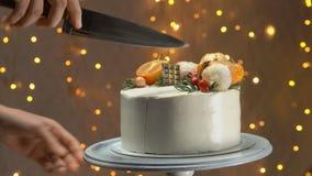 Close-up de uma mão com o bolo de ano novo dos cortes da faca filme