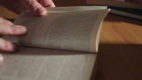Close up de uma mão do ` s do homem que lança através de um livro de papel video estoque