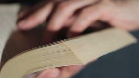 Close up de uma mão do ` s do homem que lança através de um livro de papel filme