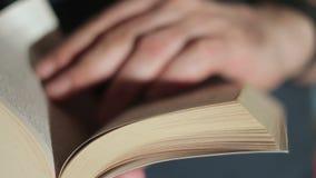 Close up de uma mão do ` s do homem que lança através de um livro de papel vídeos de arquivo