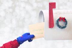 Close up de uma mão dos childs que coloca uma letra a Santa Claus em um miliampère imagem de stock