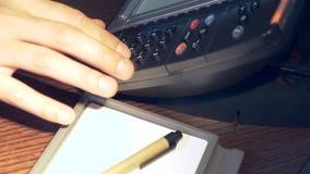 Close-up de uma mão masculina que empurra um botão em um telefone da linha terrestre em uma sala de hotel 4K vídeos de arquivo