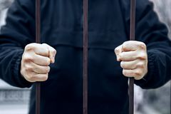 Close up de uma m?o que guarda uma gaiola de a?o, conceito do prisioneiro M?os do prisioneiro na cadeia r foto de stock royalty free